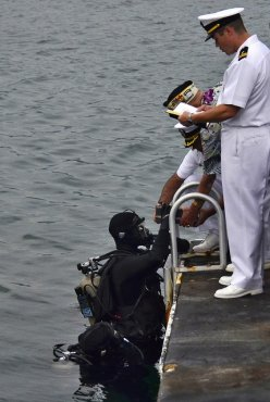 A Navy diver assists with a Pearl Harbor interment