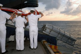 Casket of US Navy Sailor is sent over the edge of aircraft carrier during burial at sea ceremony.